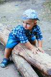 Baby Boy Sitting On A Log Stock Photography