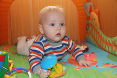 Baby boy sitting in the orange playpen Royalty Free Stock Photo