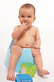 Baby boy sitting on potty Stock Images