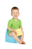 Baby boy sitting on a potty. Cute smiling baby boy with toilet paper sitting on a blue potty isolated on white background Royalty Free Stock Photography