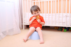Baby boy sitting on potty and eating biscuit Stock Image