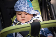 Baby boy sitting in the pram. Little and very beautiful baby boy sitting in the pram and waiting for mom Royalty Free Stock Photos