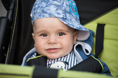 Baby boy sitting in the pram. Little and very beautiful baby boy sitting in the pram and waiting for mom Stock Photos