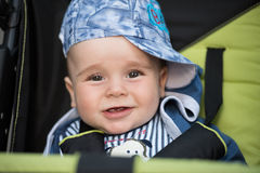 Baby boy sitting in the pram. Little and very beautiful baby boy sitting in the pram and waiting for mom Stock Images