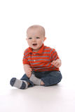 Baby boy sitting and pulling his sock off. Baby boy in red shirt sitting up and pulling off his sock Royalty Free Stock Photos