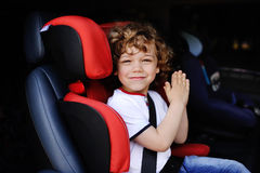 Baby boy sitting in a red child car seat Stock Photography