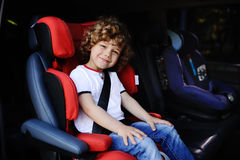 Baby boy sitting in a red child car seat Stock Photo