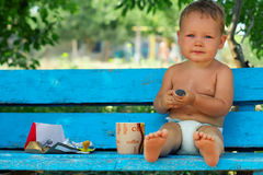 Baby boy sitting on rural bench with coffee. Morning ritual, small baby boy sitting on blue rural bench drinking coffee with chocolate Royalty Free Stock Photo