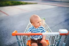 Baby boy sitting in the shopping trolley outside. Stock Photo