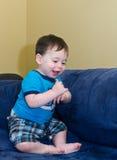 Baby boy sitting on a sofa Stock Photos