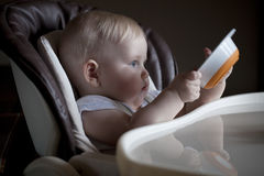 Baby boy sitting at a table for feeding with an empty plate Stock Images