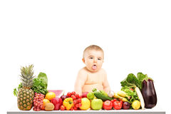 Baby boy sitting on a table full of different fruits and vegetab Royalty Free Stock Image
