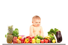 Baby boy sitting on a table full of different fruits and vegetab Stock Images