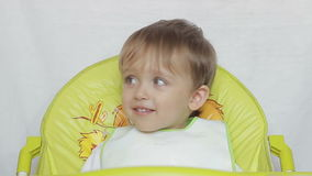 Baby boy sitting on a table laughing child eyebrows moves. stock video