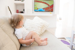 Baby boy sitting and watching cartoons. Cute baby boy sitting and watching cartoons stock photo