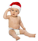 Baby boy sitting wearing Santa Claus hat. Baby boy sitting on the white background and posing looking at camera and wearing Santa Claus hat Royalty Free Stock Photos
