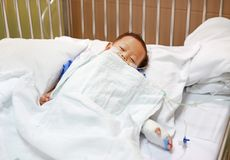 Baby boy sleeping with attaching intravenous tube to hand on bed at hospital. Baby admitted at hospital. Kid patients have IV tube.  royalty free stock photography