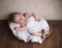 Baby boy sleeping in the basket on the wooden floor Royalty Free Stock Photos
