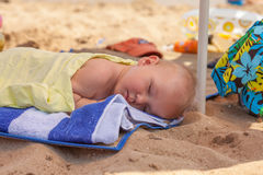 Baby boy, sleeping on the beach, exhausted after fun day at the beach Stock Photography