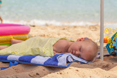 Baby boy, sleeping on the beach, exhausted after fun day at the beach Stock Images