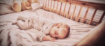 Baby boy sleeping on a cradle. At home stock images