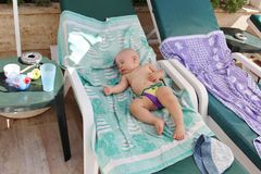 Baby boy sleeping in recliner. Nine month old bold baby boy in swimming trunks sleeping outdoor in a reclining beach chair, summer vacation concept stock photos