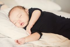Baby boy sleeping on a side. Baby boy sleeping on his side, eating in his sleep, dreaming Royalty Free Stock Photography