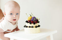 Baby boy with  small cake on two floors. Royalty Free Stock Images