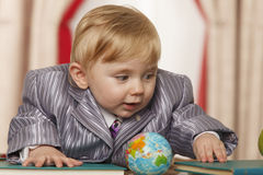 Baby boy with small globe. Surrounded books Royalty Free Stock Photo