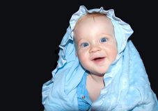 Baby boy smiles. Baby boy in blue towel smiles Stock Photography