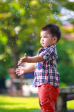 Baby boy with soap bubbles. Baby boy standing on green grass outdoor playing with soap bubbles Royalty Free Stock Photography