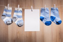 Baby boy socks. Attached to the rope and blank card for greetings Royalty Free Stock Photo