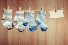 Baby boy socks. Attached to the rope and blank card for greetings Stock Photos