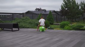 Baby boy son child jumping riding green toy horse in a green garden - Family values warm color summer scene. White caucasian stock video footage