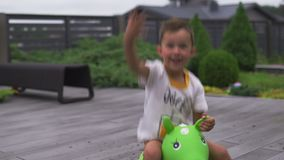 Baby boy son child jumping riding green toy horse in a green garden - Family values warm color summer scene. White caucasian stock video