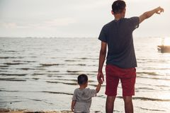 Baby boy son and father dad lifestyle happiness pointing to sea. Beach in vacation holiday royalty free stock image
