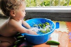 Baby boy splashing water with cucumbers Stock Image
