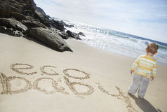 Baby Boy Standing By Eco Baby Written On Sand Royalty Free Stock Photography