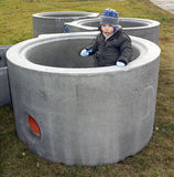 Baby boy standing inside a big concrete pipe Stock Photos