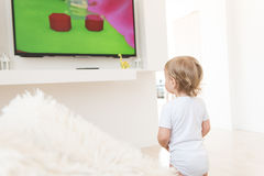 Baby boy standing up and watching cartoons. Cute baby boy standing up and watching cartoons royalty free stock photography