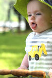 Baby boy stands and sticks out tongue in antique stroller outdoors in summer Royalty Free Stock Image
