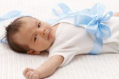 Baby boy starting to cry. Lovely baby boy in white bodysuit and big blue bow starting to cry Stock Photography