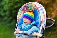 Baby boy in stroller in autumn park Stock Photo