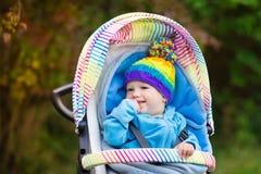 Baby boy in stroller in autumn park Stock Photography