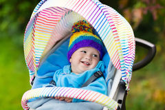 Baby boy in stroller in autumn park Stock Images