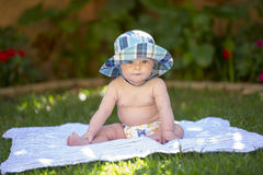 Baby boy with sunhat and cloth diaper. A baby boy sits in the shade in the garden with no shirt on and a sunhat, on a striped blanket and wearing a reusable Stock Images
