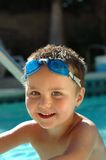 Baby boy in the swimming pool. Smiling young kid in swimming goggles standing waist-high in the pool Royalty Free Stock Images