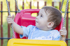Baby boy in swing Stock Images