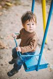 Baby boy swinging in autumn park Stock Photos