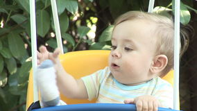 Baby boy swinging in nature stock footage